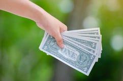 De hand verzendt het bankbiljet van de gelddollar natuurlijke achtergrondgeldbesparing en investering financieel concept stock afbeeldingen