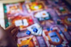 De hand werpt dobbelt op de achtergrond van Raadsspelen Stock Foto