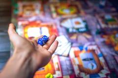 De hand werpt dobbelt op de achtergrond van Raadsspelen Stock Afbeelding