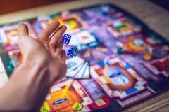 De hand werpt dobbelt op de achtergrond van Raadsspelen Royalty-vrije Stock Foto's