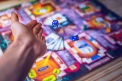 De hand werpt dobbelt op de achtergrond van Raadsspelen Royalty-vrije Stock Afbeelding