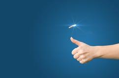 De hand werpt een muntstuk op een blauwe achtergrond voor besluitvorming stock foto