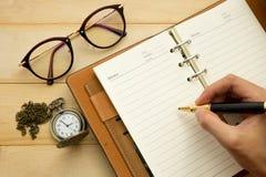 De hand wil iets en toebehoren voor het werk schrijven gezet op hout Stock Foto's