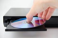De hand zet de schijf in de CD speler Stock Afbeelding