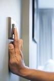 De hand zet een lichte schakelaar in een huis aan Royalty-vrije Stock Afbeeldingen