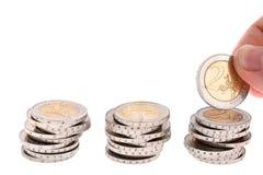 De hand zet een muntstuk twee-eur op derde muntstukkolom Stock Afbeelding