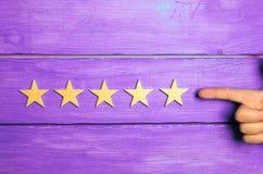 De hand zet de vijfde ster De kwaliteitsstatus is vijf sterren Een nieuwe ster, voltooiing, universele erkenning De criticus bepa stock foto's