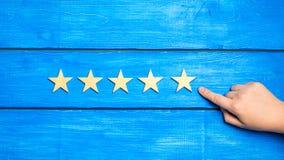 De hand zet de vijfde ster De kwaliteitsstatus is vijf sterren Een nieuwe ster, voltooiing, universele erkenning De criticus bepa royalty-vrije stock afbeelding