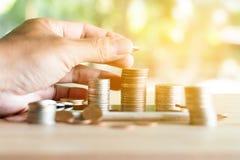 De hand zette muntstukken aan stapel muntstukken bewarend geld en inkomens of investeringsideeën en financieel beheer voor de toe stock foto's