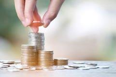 De hand zette muntstukken aan stapel van muntstukken, Besparingengeld en inkomens of Investeringsideeën en Financieel Beheer voor stock foto