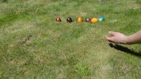 De hand zette op een rij kleurrijke geschilderde eieren en werpt hen om te verpletteren stock video