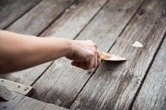De handarbeider schaaft de houten oppervlakte vlot met troffel Stock Afbeeldingen