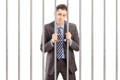 De handboeien om:doen zakenman in kostuum het stellen in gevangenis en het houden van bars stock fotografie
