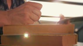 De handclose-up van de vrouw, schrijvend een nota of een brief aan een notitieboekje met een pen op een zonnige dag bij zonsonder stock footage