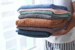 De handdoeken van de mensenholding dichtbij het venster royalty-vrije stock foto