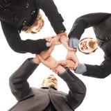 De handdruk van de groep tussen drie jonge personen stock foto
