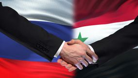 De handdruk van Rusland en van Syrië, internationale vriendschapsrelaties, vlagachtergrond stock videobeelden