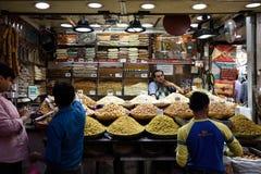 De handelaars van de kruidmarkt en vertoningen van een verscheidenheid van verse droge vruchten, noten en kruiden royalty-vrije stock afbeelding