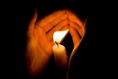 De handen beschermen helder kaarslicht in de duisternis Royalty-vrije Stock Foto's