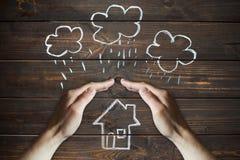 De handen beschermt een huis tegen de elementen - regen of onweer royalty-vrije stock foto's