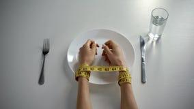 De handen bonden met tapeline op lege die plaat, meisje met het tellen van calorieën wordt geobsedeerd stock foto