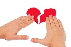 De handen combineren gebroken rood hart Stock Fotografie
