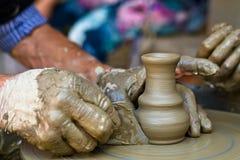 De handen die aan aardewerkwiel werken, sluiten omhoog Stock Foto