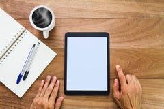 De handen die de lege computer van de het schermtablet met notitieboekje, pennen en hete koffie met behulp van vormen op houten l stock fotografie