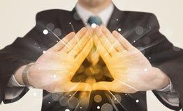 De handen die tot een vorm met geel leiden glanst Stock Fotografie
