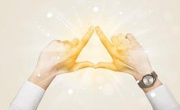 De handen die tot een vorm met geel leiden glanst Royalty-vrije Stock Foto's