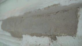 De handen die van de arbeider handschoenen dragen pleisteren nauwkeurig grijze muur met spacklemes stock video
