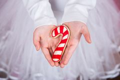 De handen die van close-upkinderen ` s Kerstmispeperkoek in vorm van karamel houden kunnen stock afbeeldingen