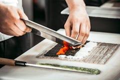 De handen die van de close-upmens s broodjes in restaurant maken Royalty-vrije Stock Afbeelding