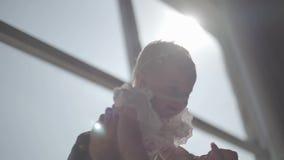 De handen die van de close-upvrouw haar glimlachend babymeisje omhoog voor groot venster opheffen De moeder die met haar kind spe stock footage