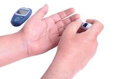 De handen die van de bloedonderzoekmens het niveau van de bloedsuiker controleren door Glucose mete Royalty-vrije Stock Fotografie