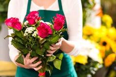 De handen die van de bloemist de rode bloemen van het rozenboeket tonen Stock Afbeelding