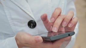 De handen die van de close-upvrouw touchscreen telefoon met behulp van stock videobeelden