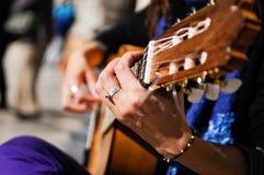 De handen die van de mens de Spaanse gitaar spelen Stock Fotografie