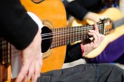 De handen die van de mens de Spaanse gitaar spelen Stock Afbeeldingen