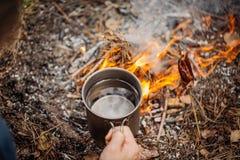 De handen die van de mensenreiziger mok met water in openlucht houden dichtbij de brand Stock Afbeelding