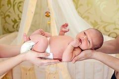 De handen die van de moeder en van de vader pasgeboren baby houden Royalty-vrije Stock Foto