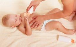De handen die van de moeder flessenmelk voor weinig boy'-lichaam houden Stock Foto