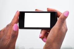 De handen die van de onderneemster mobiele telefoon in bureau houden Stock Afbeeldingen