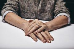 De handen die van de oude vrouw op grijze oppervlakte rusten Royalty-vrije Stock Foto's