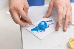 De handen die van de tandarts het blauwe materiaal van de siliconeindruk mengen Stock Foto