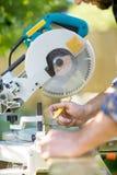 De Handen die van de timmerman op Hout bij Lijstzaag merken royalty-vrije stock afbeelding