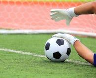 De handen die van de voetbalkeeper voor de bal bereiken stock fotografie