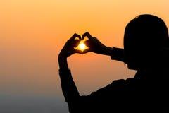 De handen die van de vrouw een hartvorm met zonsondergangsilhouet vormen Stock Foto's