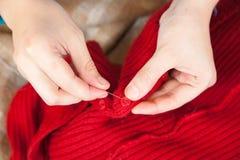 De handen die van de vrouw een knoop naaien Stock Afbeelding