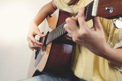 De handen die van de vrouw gitaar spelen, sluiten omhoog Uitstekende toon Royalty-vrije Stock Afbeelding